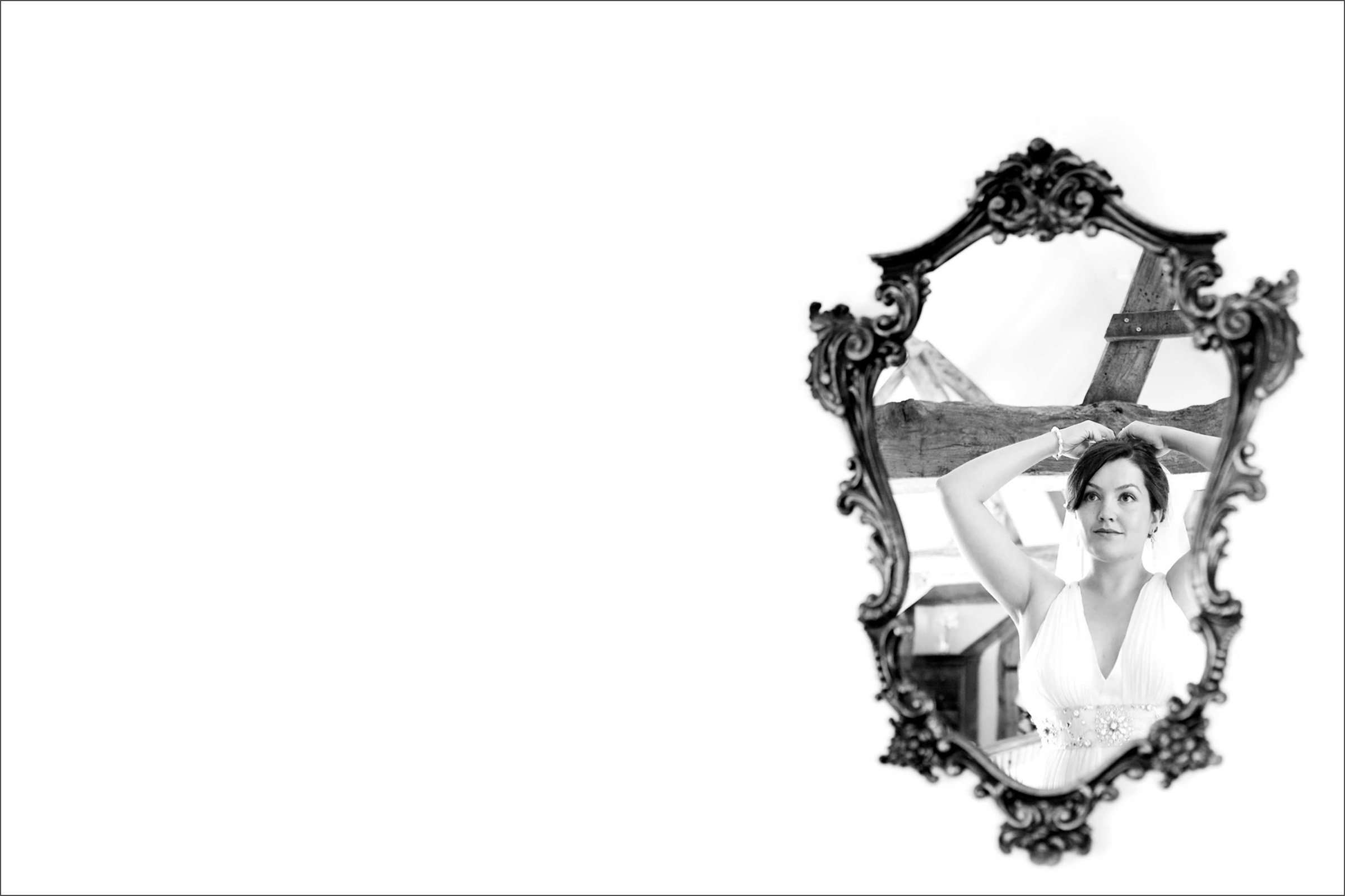 A black and white wedding photo of a bride adjusting her veil in a vintage mirror. Taken in Chichester, West Sussex