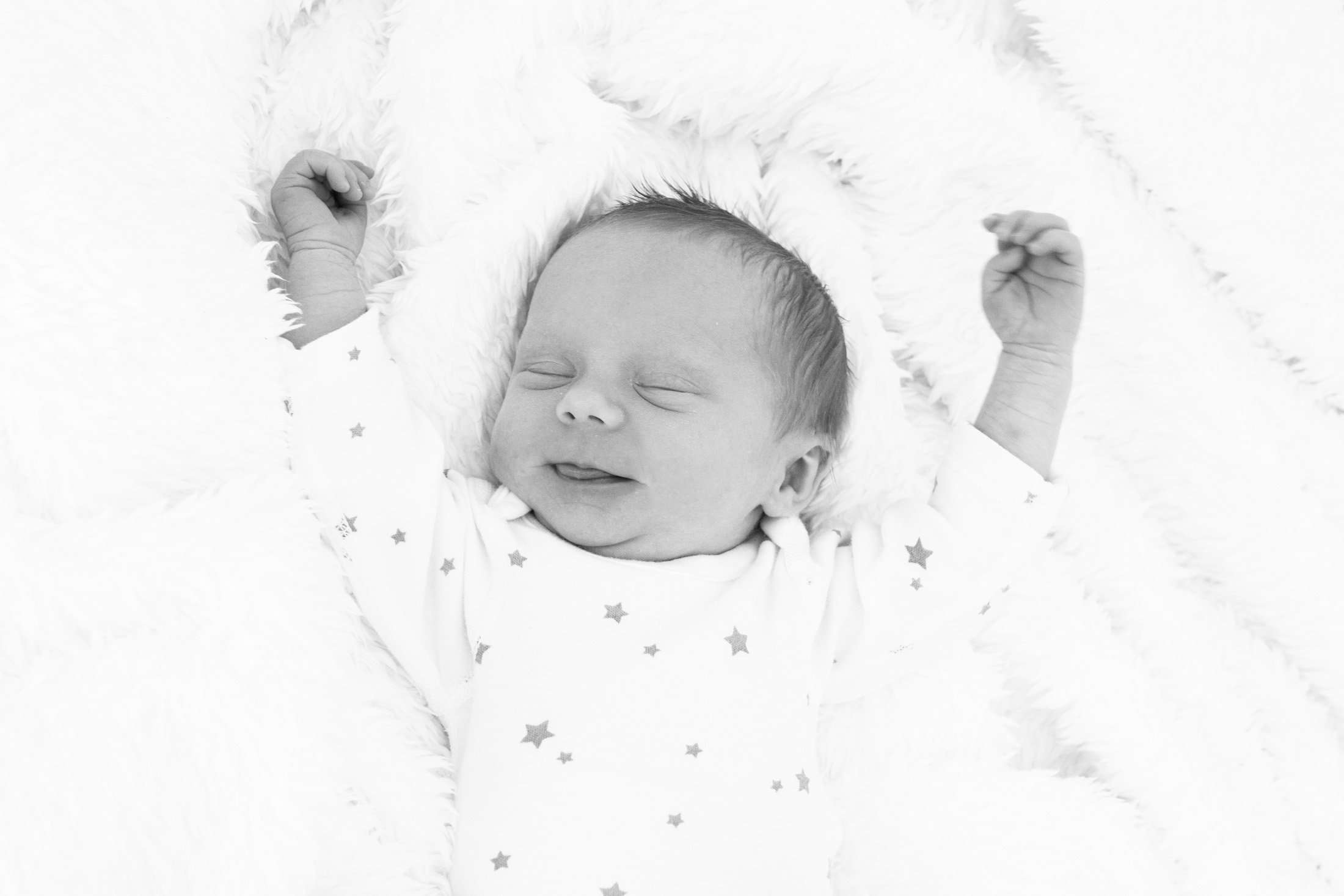 A portrait photo taken at home of a newborn baby asleep on a white blanket, taken in Chichester, Sussex